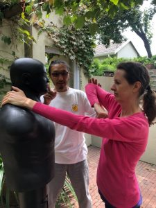 Woman learning self defense elbow strike move